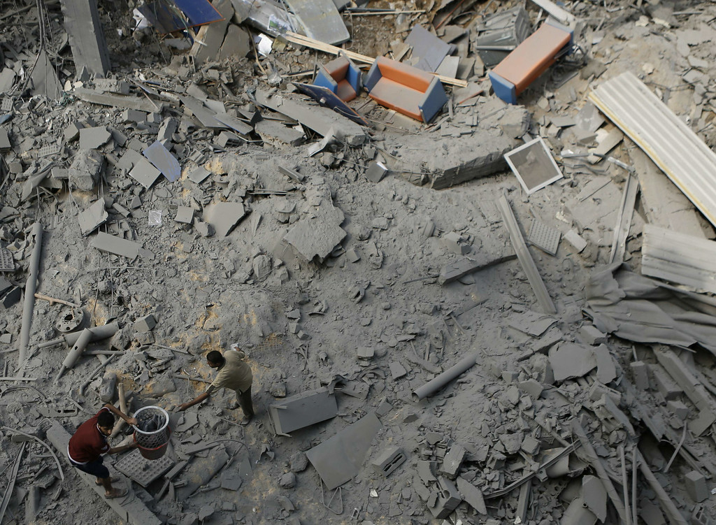 . Palestinian neighbors of the Al Aqsa television station dig through rubble after the building was destroyed in an Israeli strike in central Gaza City on July 29, 2014. Following two nights without air strikes, the violence returned to Gaza\'s skies overnight, with dozens more Palestinians killed and Israeli warplanes pounding 60 targets, among them the strips main power station and the house of a top Hamas official. AFP PHOTO/ MOHAMMED  ABED/AFP/Getty Images