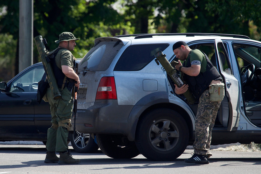 . Pro-Russian insurgents arrive with weapons, near the airport outside Donetsk, Ukraine, Monday, May 26, 2014. Ukraine\'s military launched airstrikes Monday against the separatists who had taken over the airport in the eastern city of Donetsk, suggesting that fighting in the east is far from over. (AP Photo/Ivan Sekretarev)