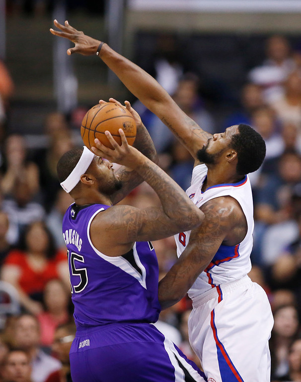 . Sacramento Kings center DeMarcus Cousins shoots the ball as Los Angeles Clippers center DeAndre Jordan defends him during the first half of an NBA basketball game in Los Angeles, Sunday, April 12, 2014. (AP Photo/Danny Moloshok)
