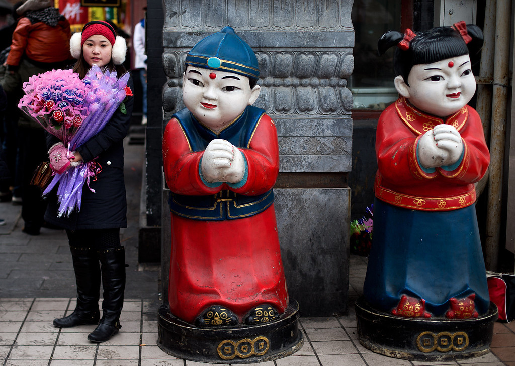 . A woman sells Valentine\'s Day roses near a pair of statue at a shopping district in Beijing, Thursday, Feb. 14, 2013. (AP Photo/Andy Wong)