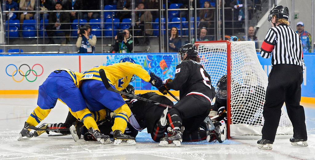 . Sweden players fight for the puck with Japan players outside the goal in the third period during the match between Sweden and Japan at the Shayba Arena in the Ice Hockey tournament at the Sochi 2014 Olympic Games, Sochi, Russia, 09 February 2014.  EPA/LARRY SMITH