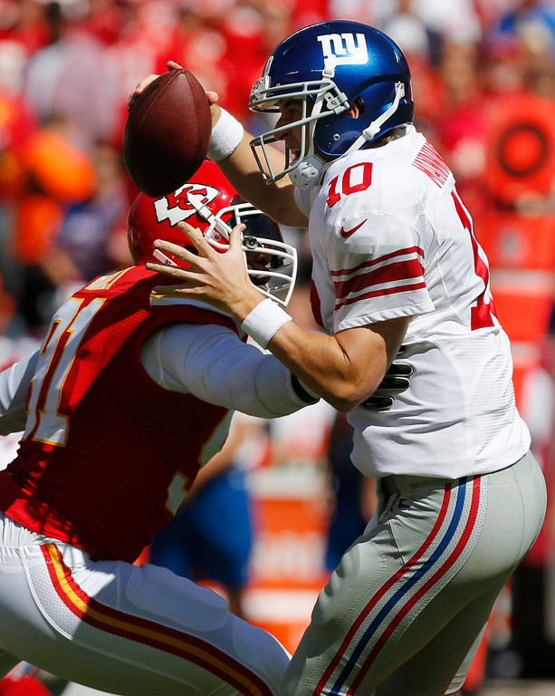 . New York Giants quarterback Eli Manning (10) avoids the rush by Kansas City Chiefs outside linebacker Tamba Hali (91) during the first half of an NFL football game at Arrowhead Stadium in Kansas City, Mo., Sunday, Sept. 29, 2013. (AP Photo/Ed Zurga)
