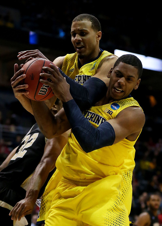 . Glenn Robinson III #1 and Jordan Morgan #52 of the Michigan Wolverines pull down a rebound against the Wofford Terriers in the second half during the second round of the 2014 NCAA Men\'s Basketball Tournament at BMO Harris Bradley Center on March 20, 2014 in Milwaukee, Wisconsin.  (Photo by Jonathan Daniel/Getty Images)