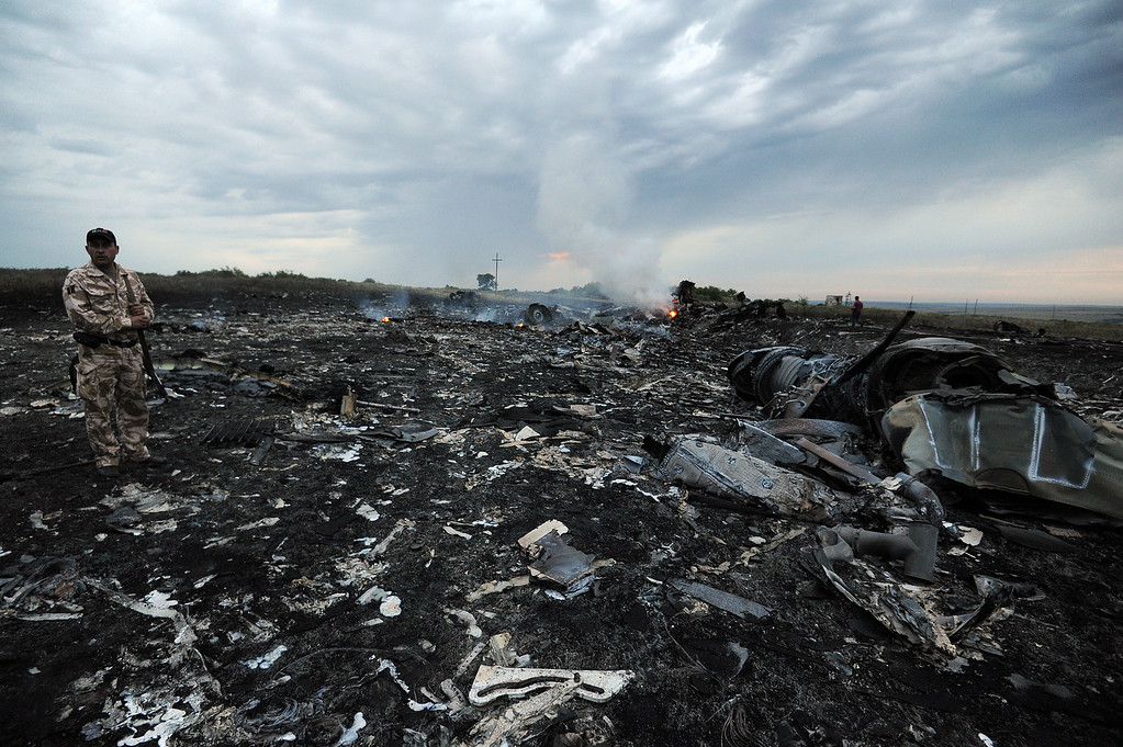 . A man wearing military fatigues stands next to the wreckages of the malaysian airliner carrying 295 people from Amsterdam to Kuala Lumpur after it crashed, near the town of Shaktarsk, in rebel-held east Ukraine, on July 17, 2014. Pro-Russian rebels fighting central Kiev authorities claimed on Thursday that the Malaysian airline that crashed in Ukraine had been shot down by a Ukrainian jet. AFP PHOTO/DOMINIQUE FAGET/AFP/Getty Images