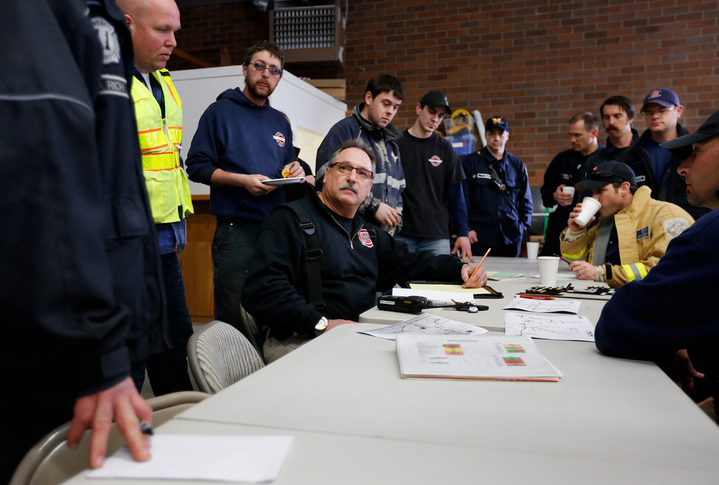 . First responders gather inside the Oso Fire Department after a fatal mudslide washed over Highway 530 and the surrounding area just east of Oso, Saturday morning, March 22, 2014. (AP Photo /The Daily Herald, Annie Mulligan)