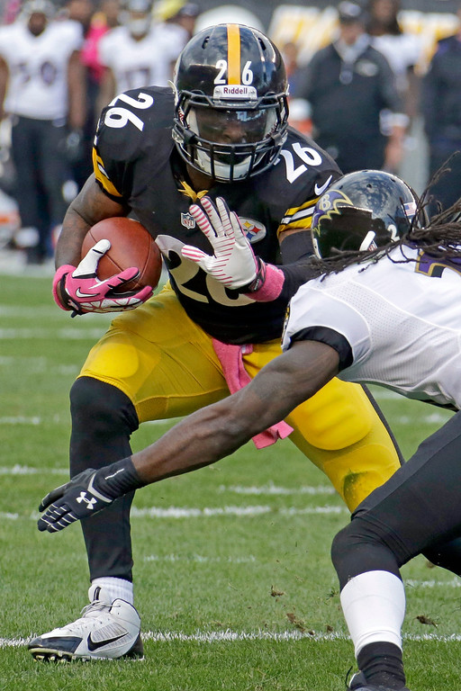 . Pittsburgh Steelers running back Le\'Veon Bell, left, runs the ball as Baltimore Ravens cornerback Lardarius Webb tries for the tackle in the first quarter of an NFL football game in Pittsburgh on Sunday, Oct. 20, 2013. (AP Photo/Gene J. Puskar)