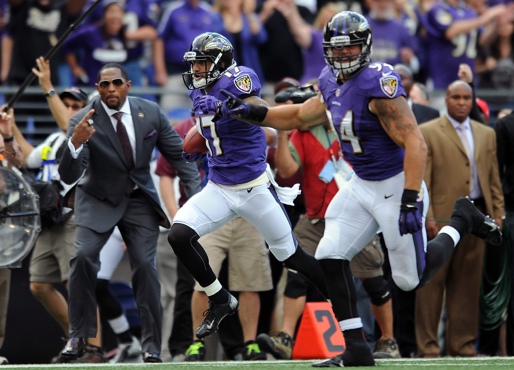 . Baltimore Ravens wide receiver Tandon Doss, center, scores an 82-yard touchdown on a punt return as former Ravens linebacker Ray Lewis, back left, cheers him on, in the first half of an NFL football game against the Houston Texans, Sunday, Sept. 22, 2013, in Baltimore. (AP Photo/Gail Burton)