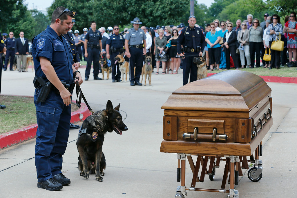. Canine officers and their handlers from around the state stopped at the casket of K-9 Kye following funeral services for the dog in Oklahoma City, Thursday, Aug. 28, 2014. (AP Photo/Sue Ogrocki)