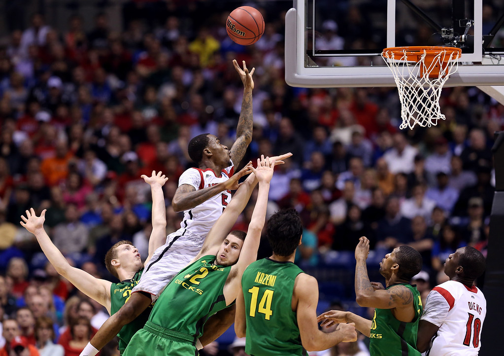 . Kevin Ware #5 of the Louisville Cardinals drives for a shot attempt in the first half against Ben Carter #32 of the Oregon Ducks during the Midwest Region Semifinal round of the 2013 NCAA Men\'s Basketball Tournament at Lucas Oil Stadium on March 29, 2013 in Indianapolis, Indiana.  (Photo by Streeter Lecka/Getty Images)