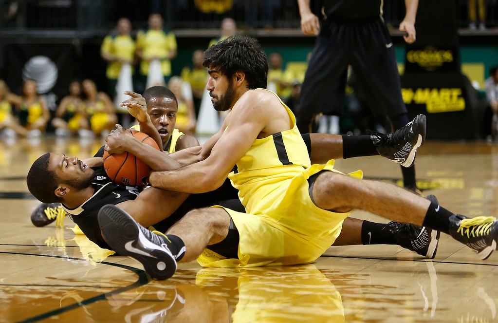 . Oregon defenders Arsalan Kazemi, center, and Johnathan Loyd, rear, tangle on the floor with Colorado\'s Jeremy Adams resulting in a jump ball during the first half of an NCAA college basketball game at Matthew Knight Arena in Eugene, Ore. Thursday, Feb. 7, 2013. (AP Photo/Brian Davies)