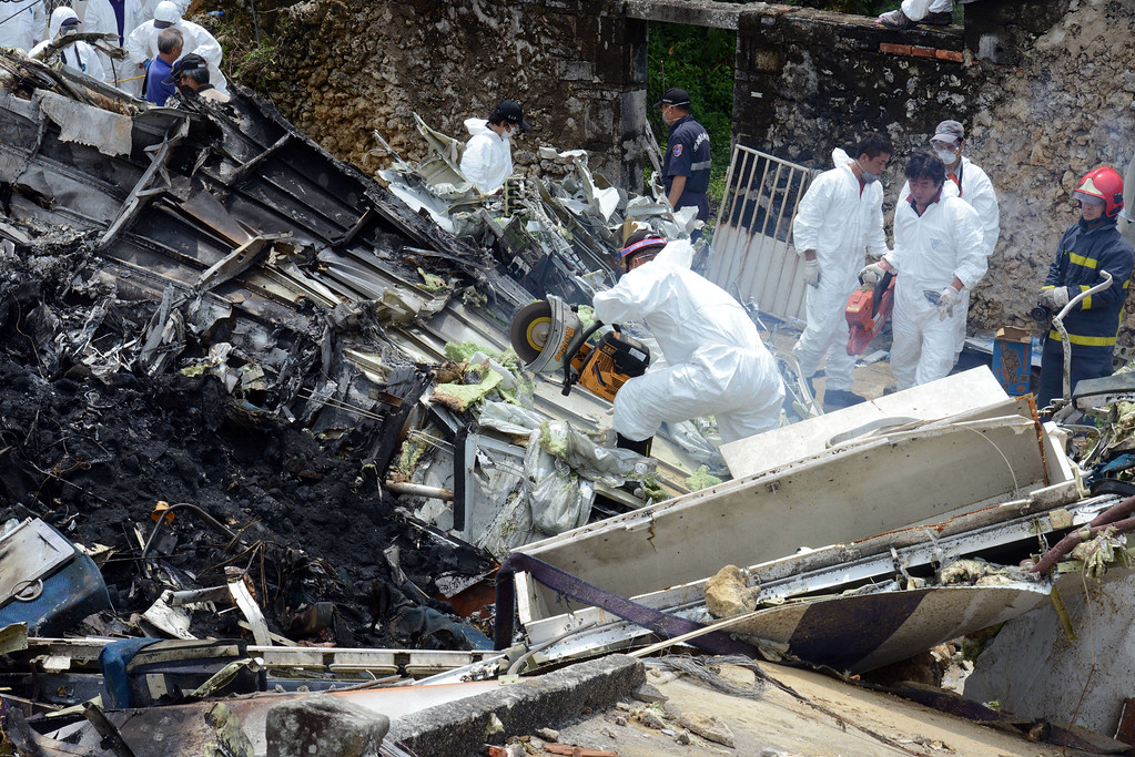 . Aviation experts cut part of the wreckage of TransAsia Airways flight GE222 the day after the ATR 72-500 plane crashed near the airport at Magong on the Penghu island chain on July 24, 2014.   AFP PHOTO / Sam YEH/AFP/Getty Images