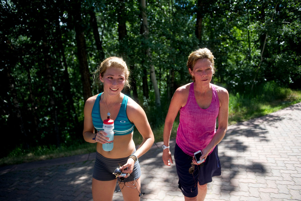 . Olympic downhill skier Mikaela Shiffrin and her mother, Eileen, rest at the top of the hill leading up to Beaver Creek, Co. after a four-mile uphill run as part of her training for this year\'s Winter Olympics on July 15, 2013. Eileen Shiffrin joined her daughter about a mile into the run.(Photo By Grant Hindsley/The Denver Post)