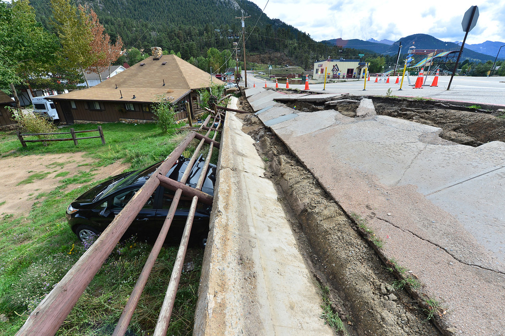 . Saturated soil collapses, bring a retaining wall down atop a parked car below Morain and Crags avenues on Friday, September 13, 2013. Saturated soil has washed away all over Estes Park. Walt Hester/Estes Park Trail-Gazette