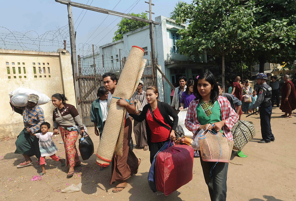 . Muslim residents carry their belongings as they evacuate their house to a temporary relief camp under police protection in riot-hit Meiktila, central Myanmar on March 22, 2013.     AFP PHOTO/Soe Than WIN/AFP/Getty Images