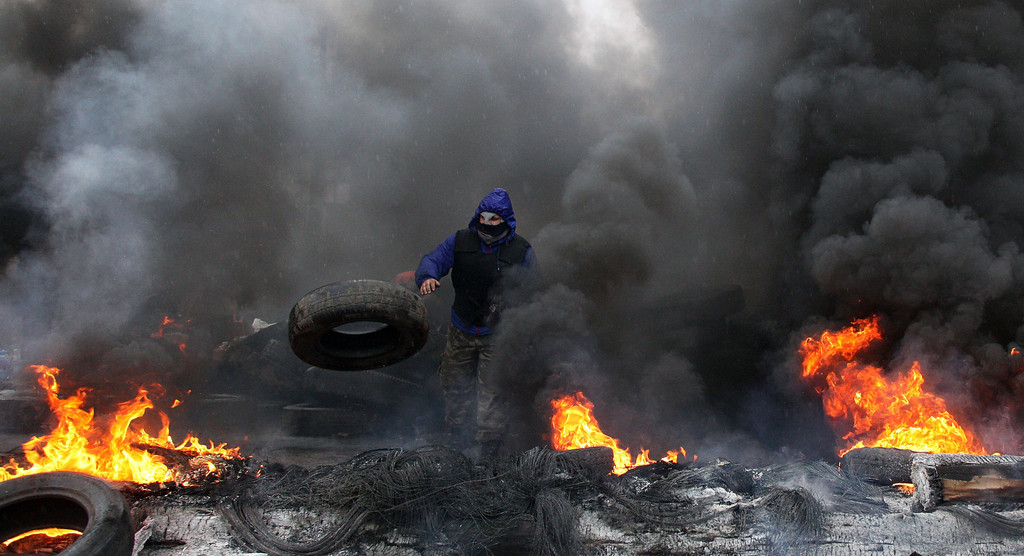 ". A pro-Russian protester burns tires in prepararation for battle with the Berkut (Ukrainian special police forces) on the outskirts of the eastern Ukrainian city of Slavyansk on April 13, 2014. Ukraine on April 13 launched an ""anti-terrorist operation\"" in the eastern town of Slavyansk, where pro-Russian gunmen have seized police and security services buildings, Interior Minister Arsen Avakov said. AFP PHOTO / ANATOLIY STEPANOV"