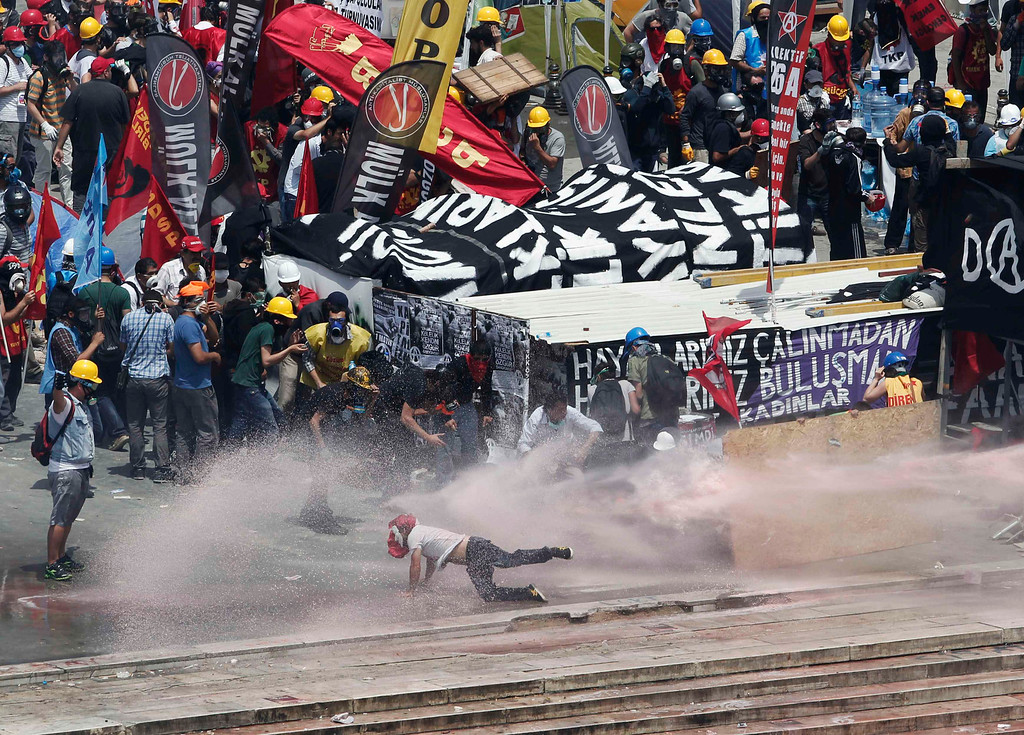 . A protester falls after being hit by a water cannon fired by riot police, as others take cover behind a makeshift shelter, during clashes at Taksim Square in Istanbul June 11, 2013.  REUTERS/Osman Orsal
