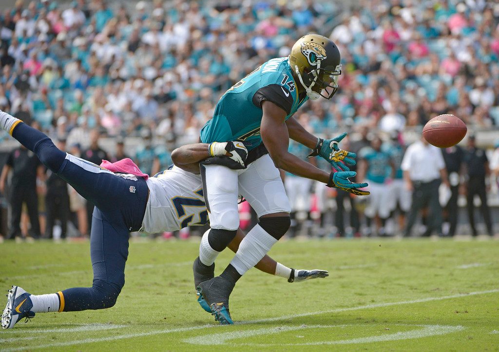 . San Diego Chargers defensive back Darrell Stuckey, left, is called for pass interference as he grabs Jacksonville Jaguars wide receiver Justin Blackmon (14) during a pass play during the first half of an NFL football game in Jacksonville, Fla., Sunday, Oct. 20, 2013.(AP Photo/Phelan M. Ebenhack)