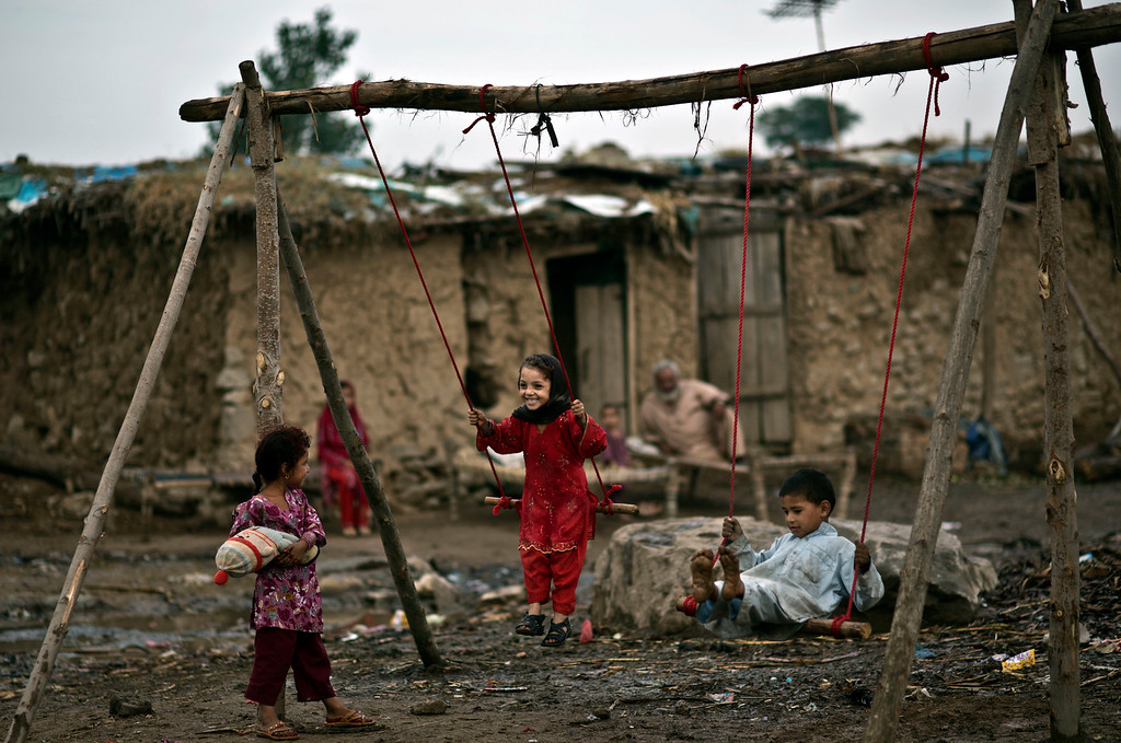 """. Afghan refugee children enjoy a ride on an improvised swing while celebrating the Muslim holiday of Eid al-Adha, or \""""Feast of Sacrifice,\"""" in a poor neighborhood on the outskirts of Islamabad, Pakistan, Thursday, Oct. 17, 2013.  (AP Photo/Muhammed Muheisen)"""