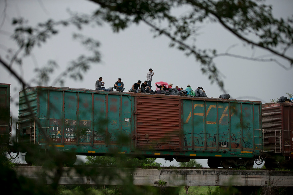 . In this Friday, June 20, 2014 photo, Central American migrants wait atop the freight train they had been traveling north on, as it starts to rain after the train suffered a minor derailment outside Reforma de Pineda, Chiapas state, Mexico. The train remained stuck in the remote wooded area for a day and a half. Migrants from Guatemala, Honduras, and El Salvador travel north through Mexico by train, by foot, or if they can afford it, by bus. Along the way, they face attacks by criminal gangs and extortion by Mexican authorities. (AP Photo/Rebecca Blackwell)
