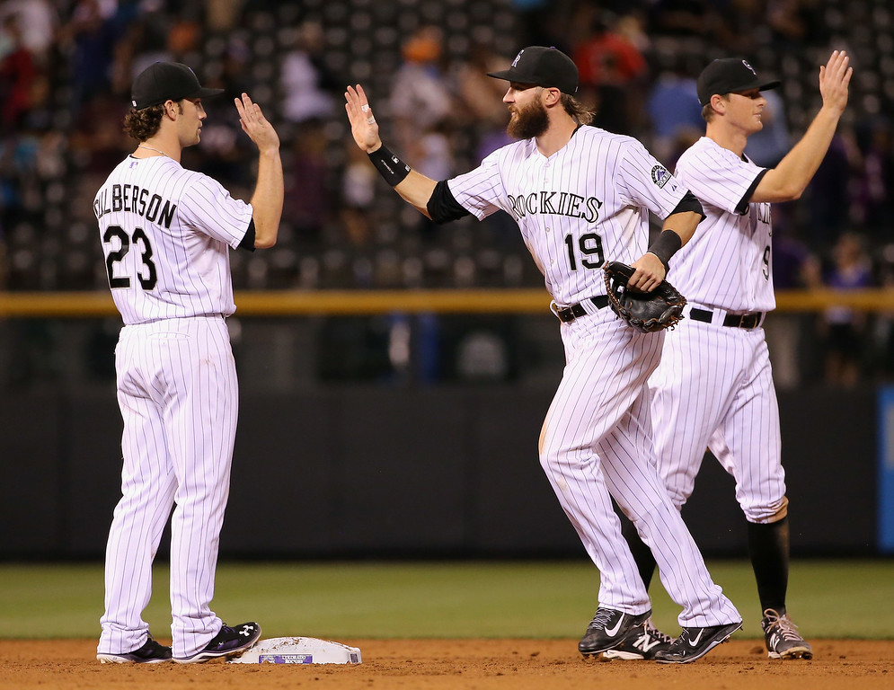 . DENVER, CO - AUGUST 14:  Charlie Culberson #23, Charlie Blackmon #19 and DJ LeMahieu #9 of the Colorado Rockies celebrate their 7-3 victory over the Cincinnati Reds at Coors Field on August 14, 2014 in Denver, Colorado.  (Photo by Doug Pensinger/Getty Images)