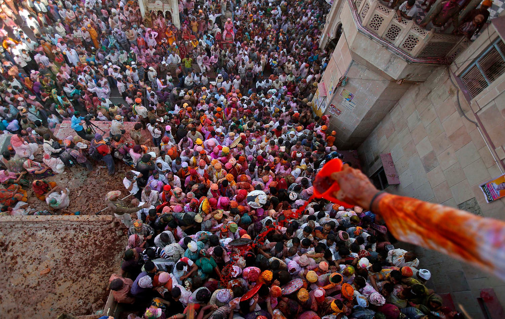 ". A Hindu devotee pours coloured water on people entering a temple during ""Lathmar Holi\"" at the village of Barsana in the northern Indian state of Uttar Pradesh March 21, 2013. In a Holi tradition unique to Barsana and Nandgaon villages, men sing provocative songs to gain the attention of women, who then \""beat\"" them with bamboo sticks called \""lathis\"". Holi, also known as the Festival of Colours, heralds the beginning of spring and is celebrated all over India. REUTERS/Vivek Prakash"