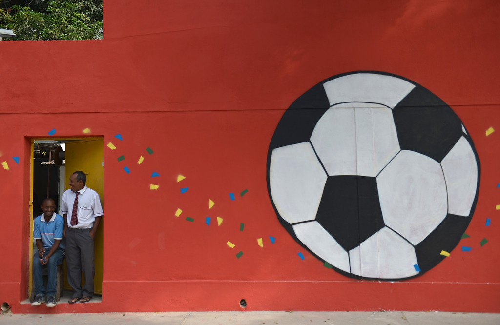 . Two men look out of a door in a wall decorated with a football mural on June 18, 2014 outside the Maracana Stadium in Rio de Janeiro during the 2014 FIFA Football World Cup.  GABRIEL BOUYS/AFP/Getty Images