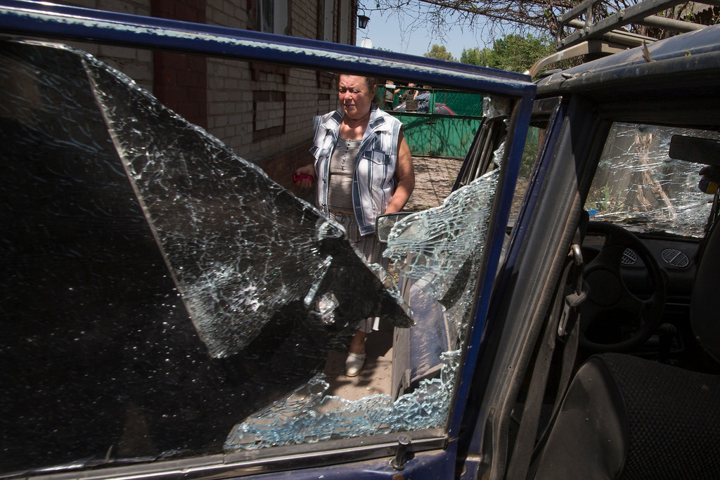 . A local woman walks past a broken car inside her yard, after a shelling from Ukrainian government forces in Slovyansk, Ukraine, Friday, May 23, 2014. The village of Semenovka on the outskirts of Slovyansk, a city that has been the epicenter of clashes for weeks, has seen continuous shelling by the Ukrainian government forces retaliating to rebel fire. Shelling continued later in the day, targeting Slovyansk, where several other buildings were also damaged. There was no word of casualties. (AP Photo/Alexander Zemlianichenko)