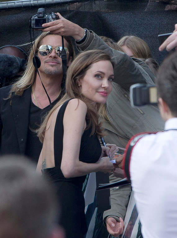 . Brad Pitt and Angelina Jolie pose with fans as they arrive for the World Premiere of World War Z  at a central London cinema, Sunday, June 2, 2013. (Photo by Joel Ryan/Invision/AP)