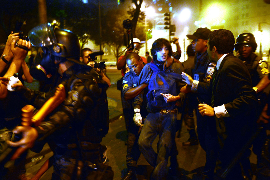 """. Policemen arrest a demonstrator during clashes after a protest for the \""""Teachers\' day\"""", on October 15, 2013 in Rio de Janeiro, Brazil. AFP PHOTO / YASUYOSHI CHIBA/AFP/Getty Images"""