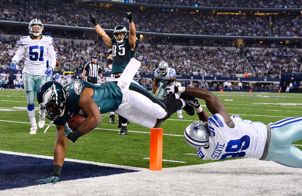 . Philadelphia Eagles player Bryce Brown (L) scores a touchdown against Dallas Cowboys player George Selvie (R) in the second half of their game at AT&T Stadium in Arlington, Texas, USA, 29 December 2013.  EPA/LARRY W. SMITH