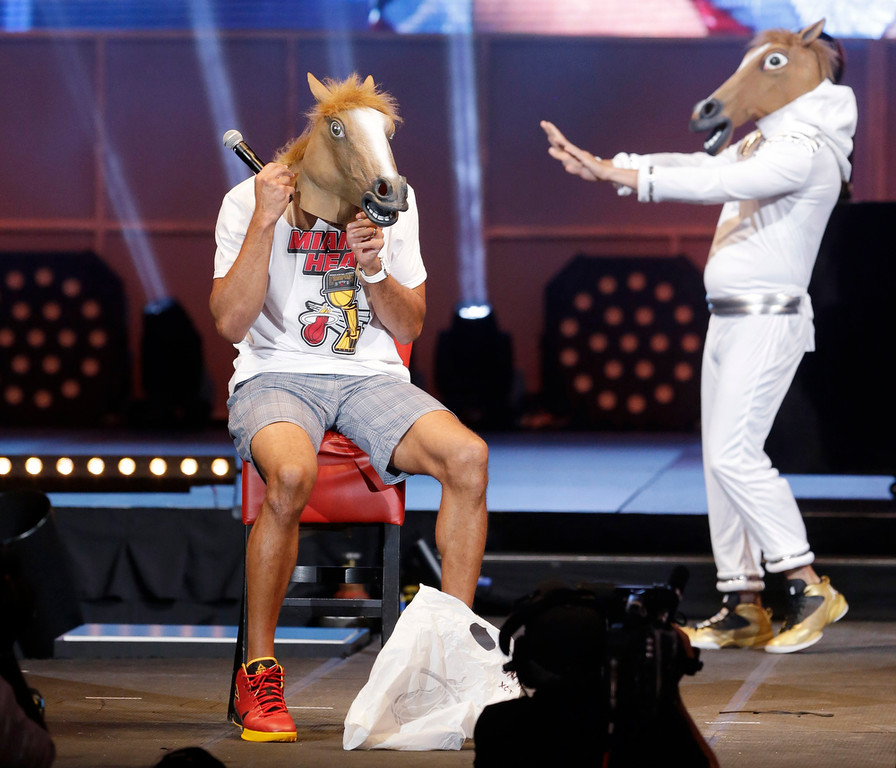 . Miami Heat forward Shane Battier, foreground puts on a horse head mask as an unidentified person in a mask dances behind him, Monday, June 24, 2013, during a celebration for season ticket holders at the American Airlines Arena in Miami. The Heat defeated the San Antonio Spurs 95-88 in Game 7 to win their second straight NBA basketball championship. (AP Photo/Wilfredo Lee)