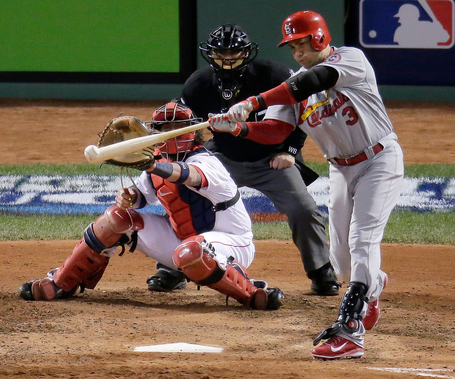 . St. Louis Cardinals\' Carlos Beltran hits an RBI single in front of Boston Red Sox catcher Jarrod Saltalamacchia during the seventh inning in Game 2 of baseball\'s World Series Thursday, Oct. 24, 2013, in Boston. (AP Photo/Charlie Riedel)
