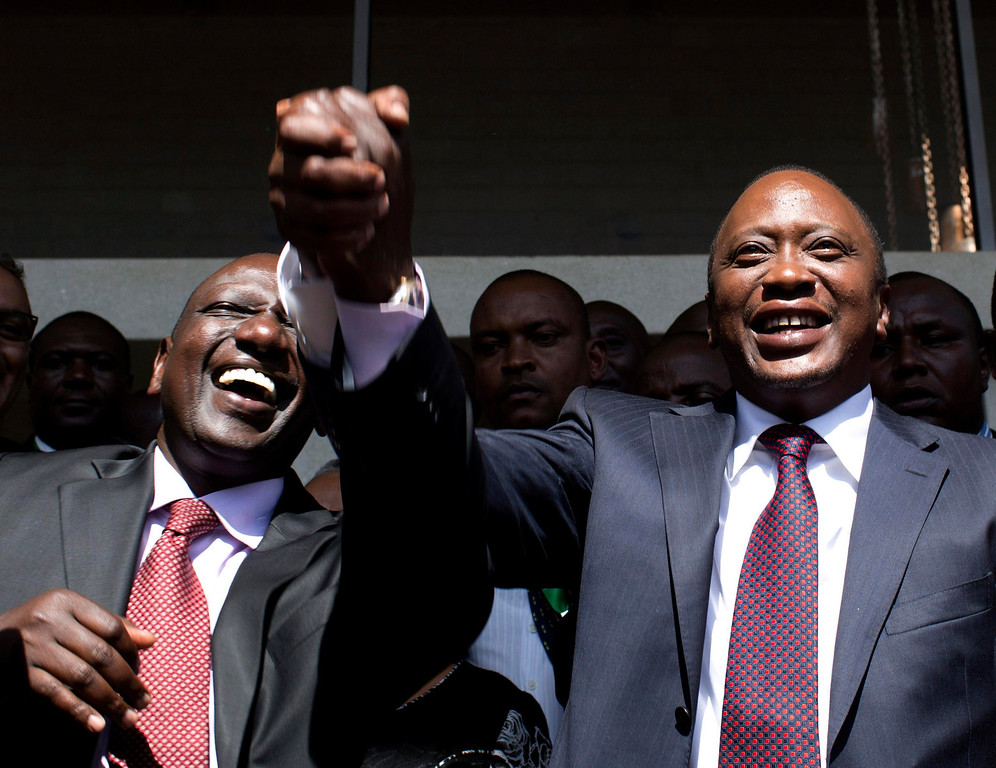. President-elect Uhuru Kenyatta (R) greets his supporters with his running mate, former cabinet minister William Ruto after attending a news conference in Nairobi March 9, 2013. Kenyatta, indicted for crimes against humanity, was declared winner of Kenya\'s presidential election on Saturday with a tiny margin, just enough to avoid a run-off after a race that has divided the nation along tribal lines. REUTERS/Siegfried Modola