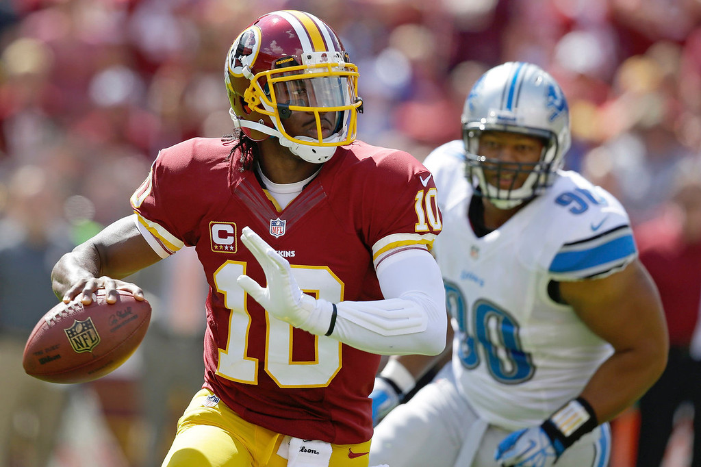 . Washington Redskins quarterback Robert Griffin III scrambles away from Detroit Lions defensive tackle Ndamukong Suh, right, during the first half of a NFL football game in Landover, Md., Sunday Sept. 22, 2013. (AP Photo/Alex Brandon)