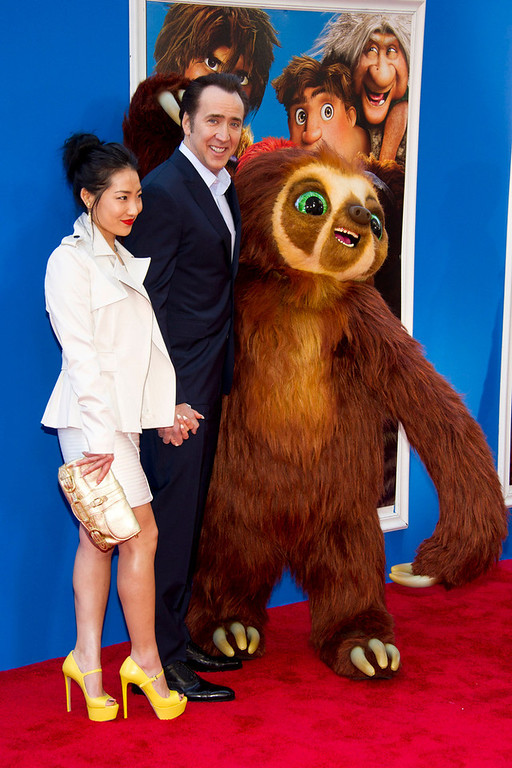 """. Nicolas Cage and his wife, Alice Kim, pose with Belt the sloth at \""""The Croods\"""" premiere on Sunday, March 10, 2013 in New York. (Photo by Charles Sykes/Invision/AP)"""