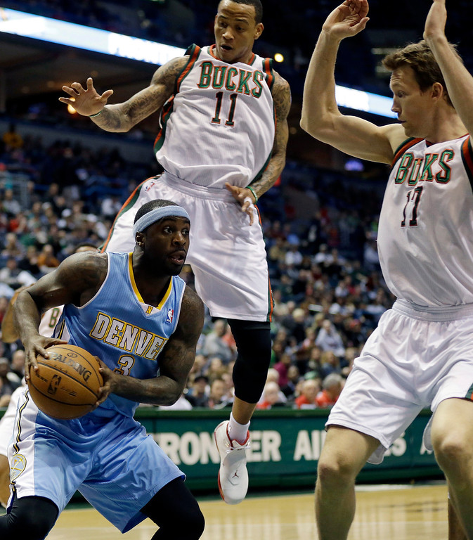 . Denver Nuggets\' Ty Lawson (3) drives against Milwaukee Bucks\' Monta Ellis (11) and Mike Dunleavy, right, during the first half of an NBA basketball game on Monday, April 15, 2013, in Milwaukee. (AP Photo/Jeffrey Phelps)