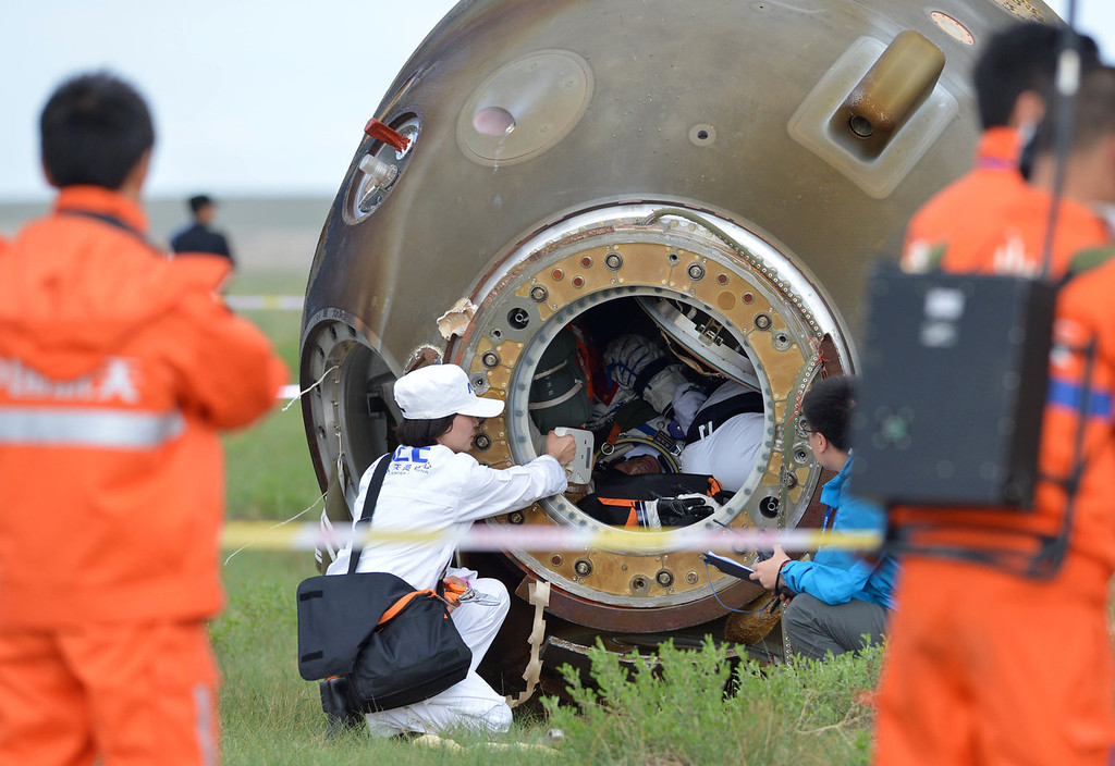. Technicians inspect the return capsule of the Shenzhou-10 spacecraft carrying three Chinese astronauts after it landed in the grasslands of north China\'s Inner Mongolia region on June 26, 2013, following a 15-day mission in space. China completed its longest manned space mission on June 26 as its Shenzhou-10 spacecraft and three crew members safely returned to Earth, in a major step towards Beijing\'s goal of building a permanent space station by 2020.  AFP PHOTOAFP/AFP/Getty Images
