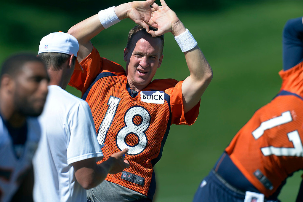 . Denver Broncos quarterback Peyton Manning (18) stretches as he talks with offensive coordinator Adam Gase before practice  September 3, 2013 at Dove Valley. (Photo by John Leyba/The Denver Post)