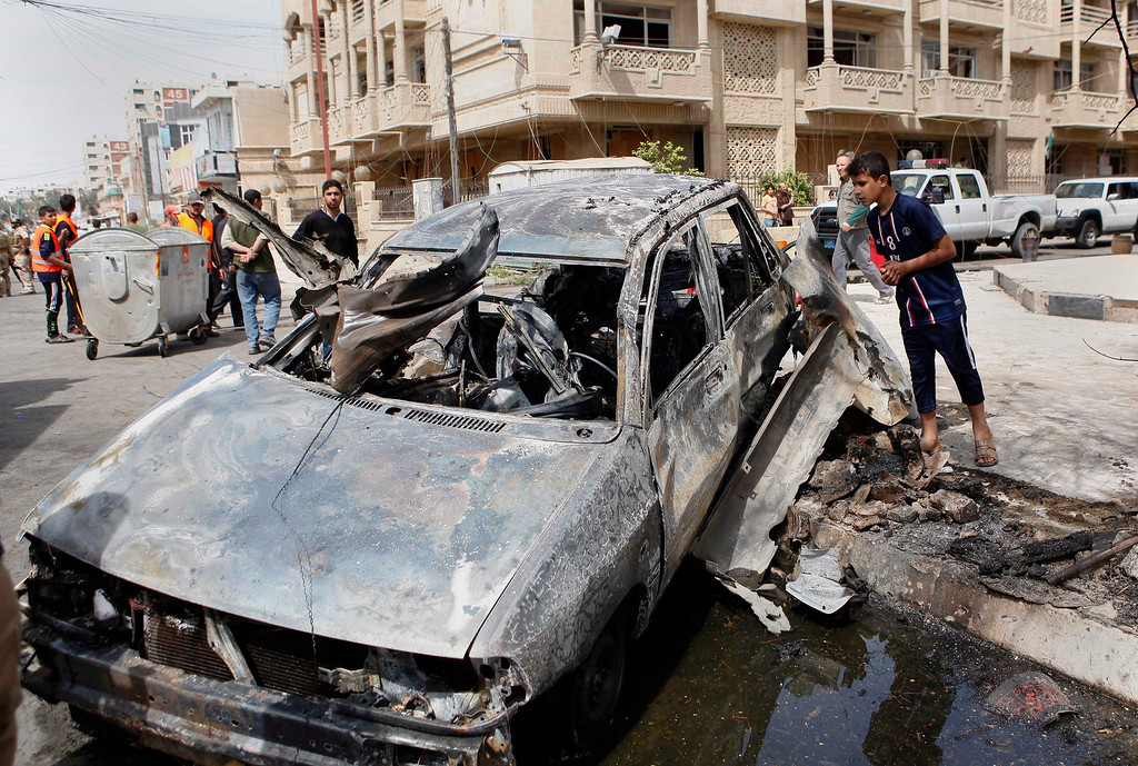 . People inspect a car destroyed in a car bomb attack close to one of the main gates to the heavily-fortified Green Zone, which houses major government offices and the embassies of several countries, including the United States and Britain in Baghdad, Iraq, Tuesday, March 19, 2013. (AP Photo/ Hadi Mizban)