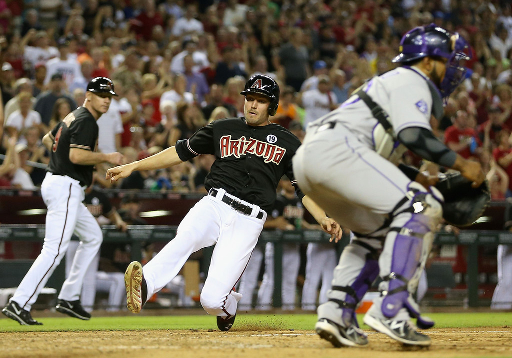 . PHOENIX, AZ - JULY 05:  A.J. Pollock #11 of the Arizona Diamondbacks slides in to score a run past catcher Wilin Rosario #20 of the Colorado Rockies during the seventh inning of the MLB game at Chase Field on July 5, 2013 in Phoenix, Arizona.  (Photo by Christian Petersen/Getty Images)