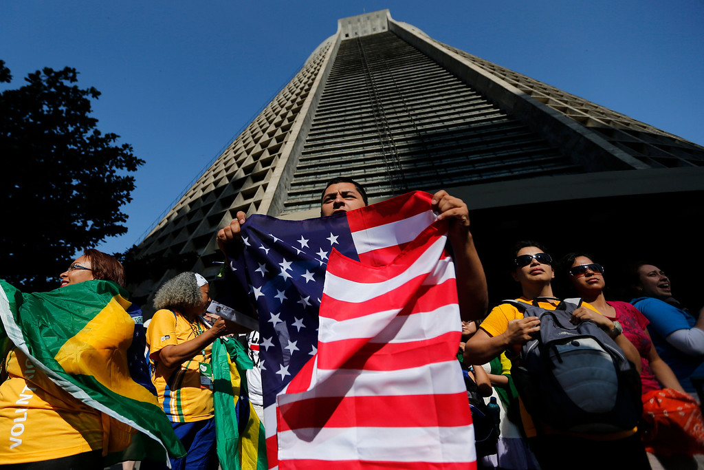 . Faithful holding a Brazilian flag, left, and a U.S. flag, right, gather outside Rio de Janeiro\'s cathedral, background, as they wait for the arrival of Pope Francis to Rio de Janeiro, Brazil, Monday, July 22, 2013. (AP Photo/Victor R. Caivano)