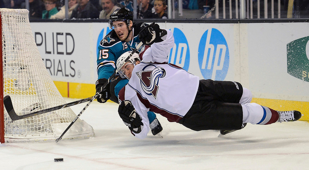 . Aaron Palushaj #17 of the Colorado Avalanche falls to the ice attempting to maintain control of the puck away from James Sheppard #15 of the San Jose Sharks in the first period at HP Pavilion on February 26, 2013 in San Jose, California.  (Photo by Thearon W. Henderson/Getty Images)