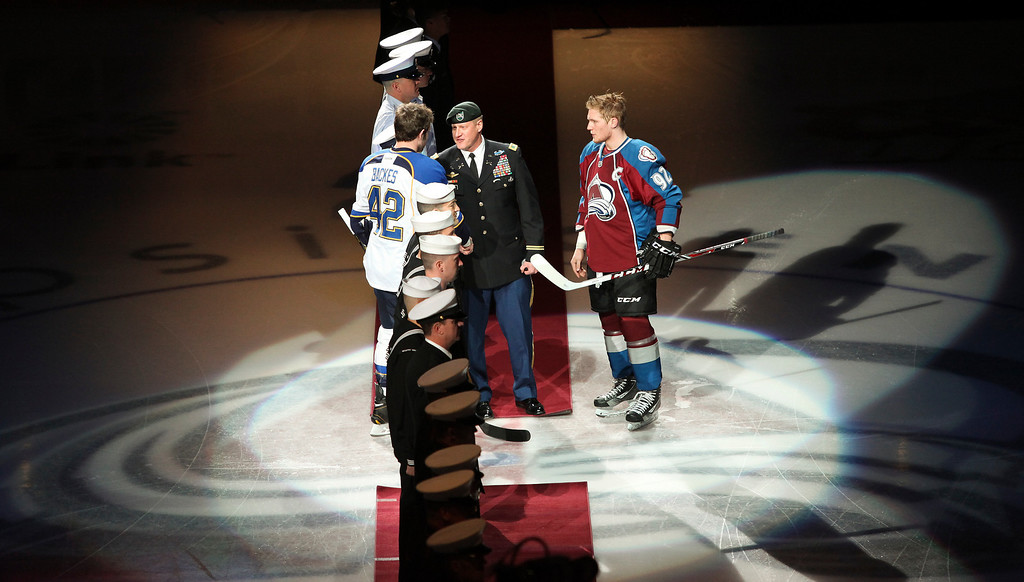. St. Louis Blues Captian David Backes (42) and Colorado Avalanche Captian Gabriel Landeskog (92) meet Army Col. David Grosso before an NHL hockey game on Sunday, April 21, 2013 in Denver. (AP Photo/Barry Gutierrez)
