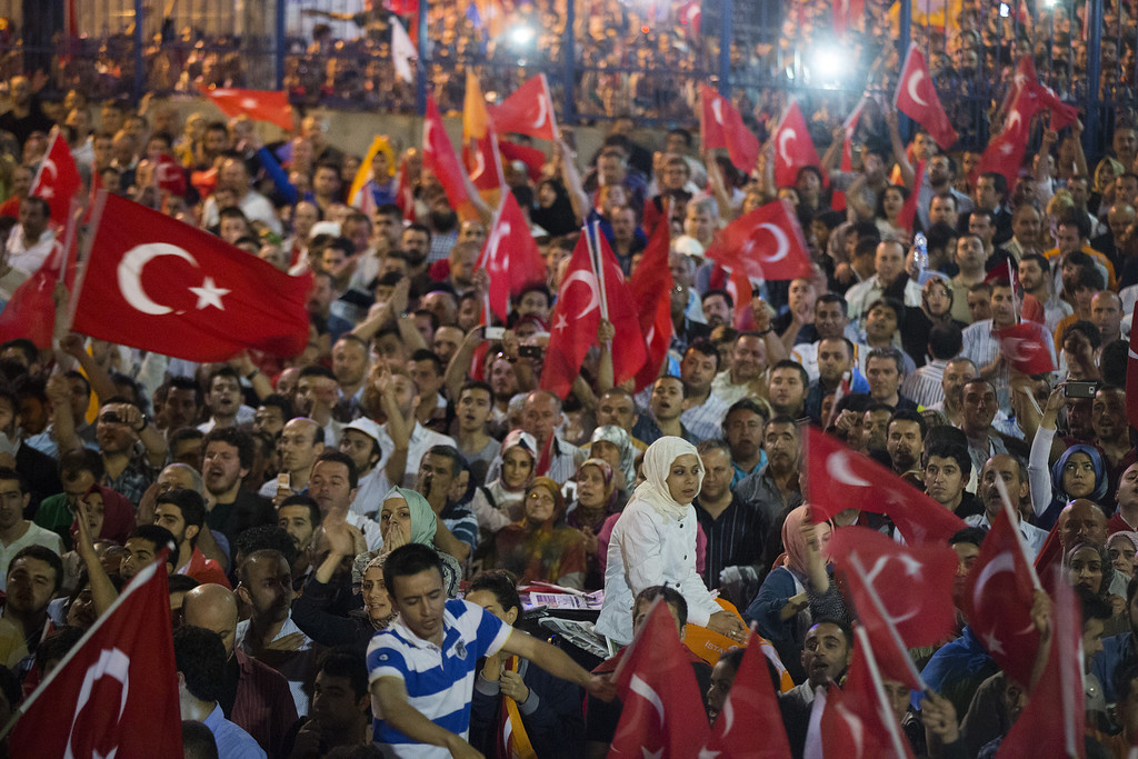 . ISTANBUL, TURKEY - JUNE 07:  Supporters of Turkish prime minister Recep Tayyip Erdogan wave their national flag on June 7, 2013 in Istanbul, Turkey. Thousands of supporters greeted the prime minister at Istanbul airport on his return from a North African tour, while thousands more protestors rallied again in Istanbul\'s Taksim Square.  (Photo by Uriel Sinai/Getty Images)