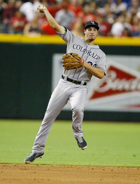 . Colorado Rockies third baseman Nolan Arenado  makes the off balance throw against the Arizona Diamondbacks in the third inning during a baseball game on Saturday, July 6, 2013, in Phoenix. (AP Photo/Rick Scuteri)