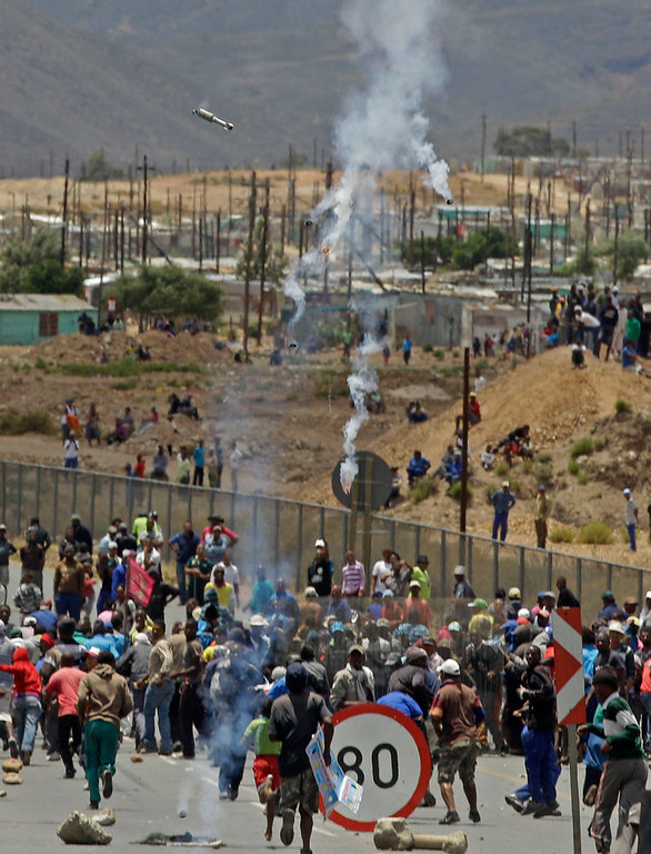 . Striking farm workers run away from South African Police as tear gas canisters, top center, fall from the sky,  during their demonstrate in De Doorns , South Africa, Thursday, Jan 10, 2013. Striking farm workers in South Africa have clashed with police for a second day during protests for higher wages. The South African Press Association says police on Thursday fired rubber bullets at rock-throwing demonstrators in the town of De Doorns in Western Cape province, and protests were occurring in at least two other towns. (AP Photo/Schalk van Zuydam)