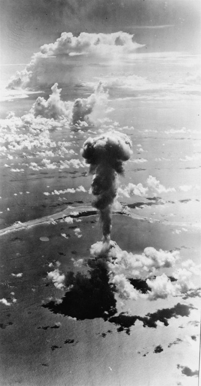 . A mushroom-topped column of smoke and gas, brighter than the sun, rises through a disintegrating vapor cloud over Bikini Lagoon in the aerial bomb test July 1, 1946.  Because of the brightness, no part of the column is in the shadow of the sun which is shining across Bikini at the left.  The cloud ring is the remains of the cloud of vapor, or fog, which enveloped the  fireball  the instant after the explosion.  The cloud disappeared quickly.  The shock wave, visible as a circle around the explosion area, is about half way to Bikini Island, approximately three miles from the point of explosion. (AP Photo)
