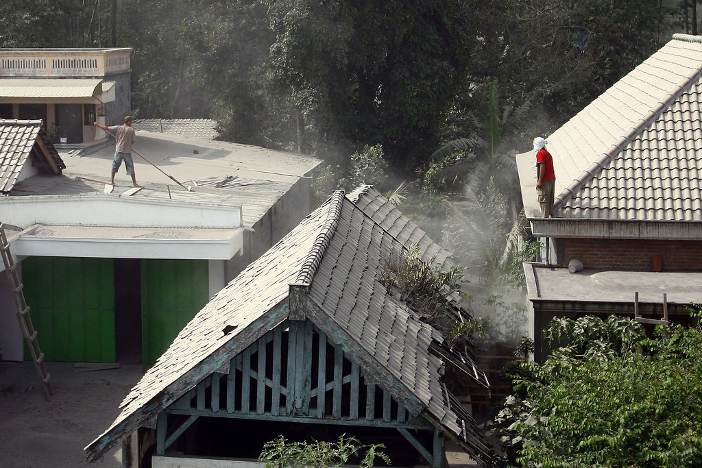 . Residents clean ash covered roofs in the village of Kediri in East Java province on February 14, 2014 following the eruption of Mount Kelud volcano.  AFP PHOTO / JUNI KRISWANTO/AFP/Getty Images