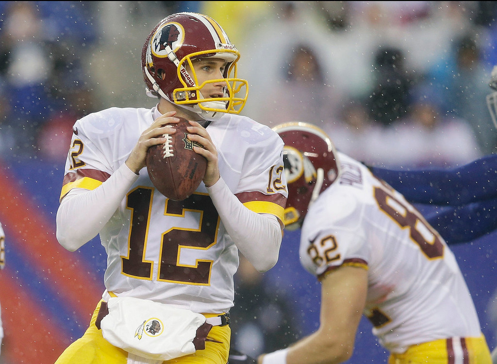 . In the rain, Washington Redskins quarterback Kirk Cousins (12) looks to pass during the first half of an NFL football game against the New York Giants, Sunday, Dec. 29, 2013, in East Rutherford, N.J.  (AP Photo/Julio Cortez)