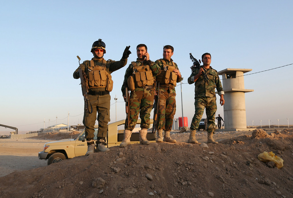 . Kurdish Peshmerga fighters stand guard during airstrikes targeting Islamic State militants near the Khazer checkpoint outside of the city of Irbil in northern Iraq, Friday, Aug. 8, 2014.  (AP Photo/Khalid Mohammed)